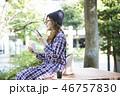 公園でスマホを見る女性  46757830