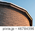 Snowy roof over curved brick wall with light gradient 46784396
