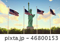 The American flags flutters in the wind on a sunrise against the blue sky and the Statue of Liberty 46800153