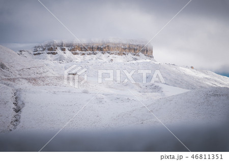 Winter landscape of snow-covered cliffs of the plateau in the North Caucasus through the branches of 46811351