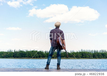 man with guitar on the river. 46822936