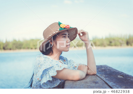 Young woman sitting on the lake pier 46822938