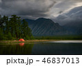 Orange tent on coast of lake at night. 46837013