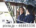 お寺の前で停車する人力車に乗る二人の女子高生 46865336
