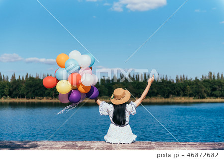 Happy young woman playing with balloons 46872682