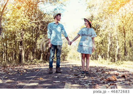 couple holding hands and walking through pathway 46872683