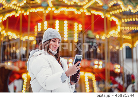 A beautiful young woman or girl using phone outdoor Christmas holidays background. 46881544