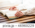 Female hands with book on a wooden table 46960229