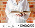 Woman in white shirt holding old book 46960255