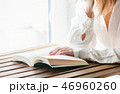 Female hands with book on a wooden table 46960260