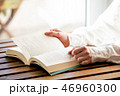 Female hands with book on a wooden table 46960300