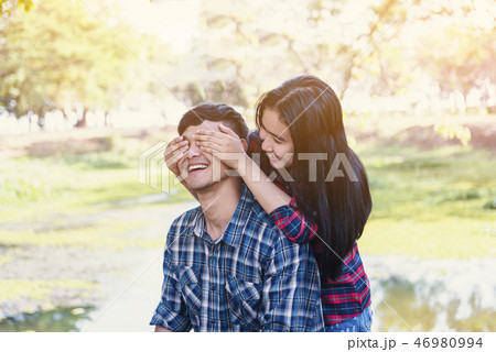 Woman covering eyes to young surprising girlfriend 46980994