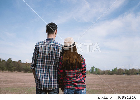 couple in love holding hands in the meadow 46981216