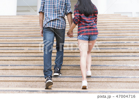 couple boy and girl hold hands and go up the stair 47004716