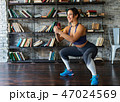 Woman doing squat workout and smiling during fitness training at home 47024569