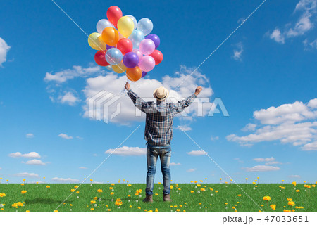 man with holding balloon in blue sky  47033651