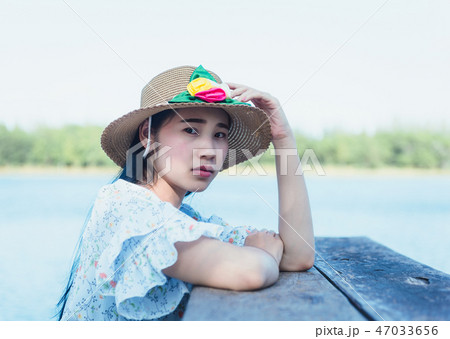 Young beautiful hipster woman sitting on the lake 47033656