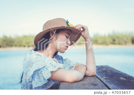 Young beautiful hipster woman sitting on the lake 47033657