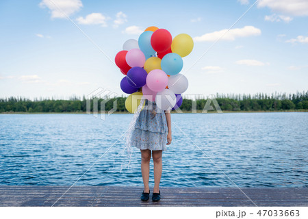 Happy young woman playing with balloons 47033663