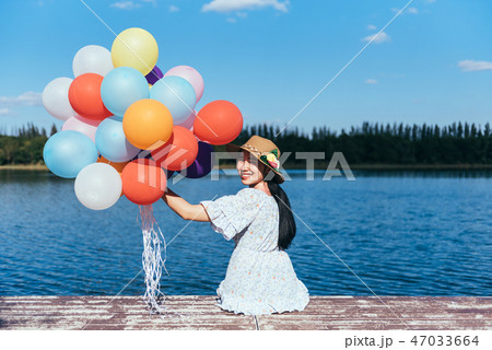 Happy young woman playing with balloons 47033664