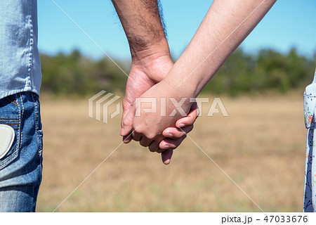Romantic couple with clasped hands backlit 47033676