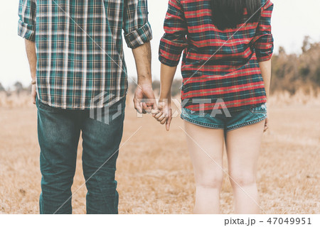 couple with clasped hands backlit 47049951