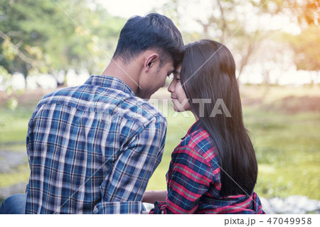 young asian couple hugging outdoors.  47049958