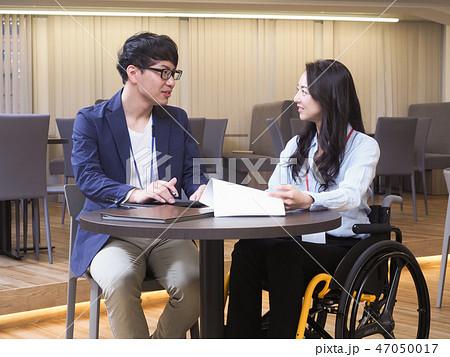 日本ユニバーサルマナー協会監修素材 車椅子に乗ったビジネスウーマンのミーティングシーン 47050017