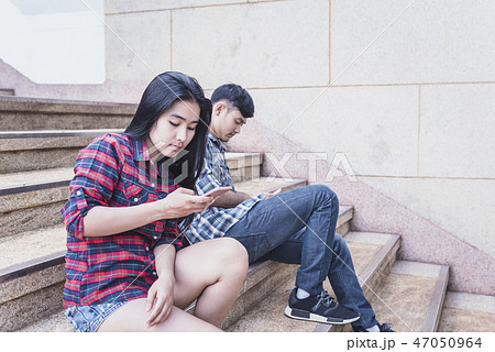couple lying on the staircase with smartphones  47050964