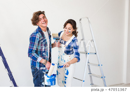 People, redecoration and relationship concept - Young funny couple doing renovation in new apartment 47051367