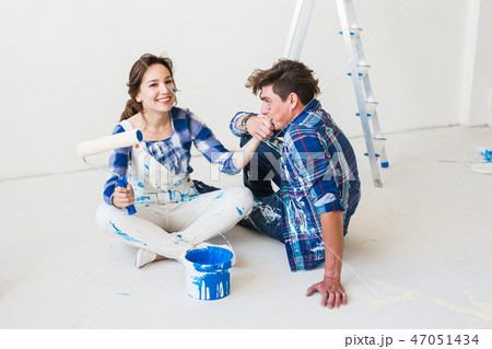 People, redecoration and relationship concept - Young funny couple doing renovation in new apartment 47051434
