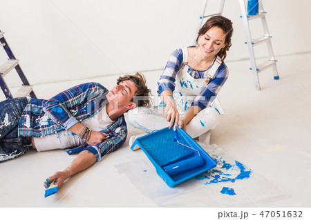 Smiling loving couple doing home renovations. Young woman is holding a paint roller and young man is 47051632