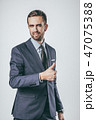 Confident man in suit gesturing thumb up 47075388
