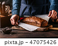 Woman putting freshly baked bread on board 47075426