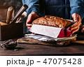 Woman serving grain loaf of bread 47075428