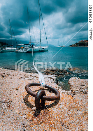 Mooring rope and bollard on sea water and yacht at the background. Dramatic Rainy clouds above 47093304