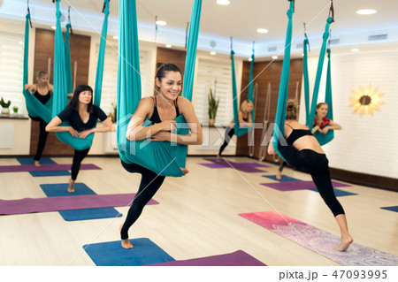 group of womans doing fly yoga stretching exerciseの写真素材