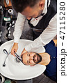 A top view of hipster man client visiting haidresser and hairstylist in barber shop. 47115280