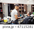 Rear view of man client visiting haidresser and hairstylist in barber shop. 47115281