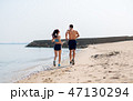 couple in sports clothes running along on beach 47130294