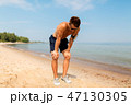 male runner with earphones and arm band on beach 47130305