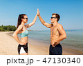 happy couple in sports clothes and shades on beach 47130340