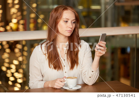 woman with coffee and smartphone at restaurant 47130541