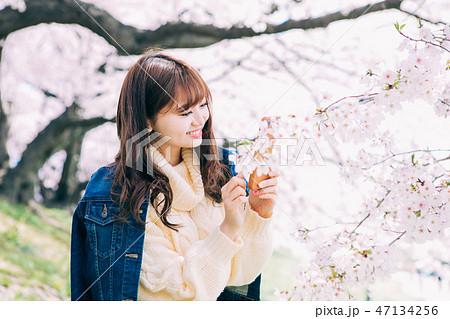 スマホで桜を撮る女性 47134256