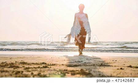 Beautiful female angel walking barefoot toward the sea at sunset. 47142687