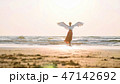 Beautiful female angel walking barefoot toward the sea at sunset. 47142692