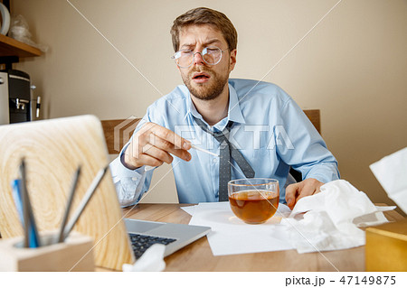 Sick man while working in office, businessman caught cold, seasonal flu. 47149875