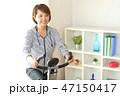フィットネスバイクで体を鍛える女性 47150417