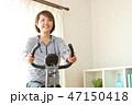 フィットネスバイクで体を鍛える女性 47150418