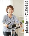 フィットネスバイクで体を鍛える女性 47150419